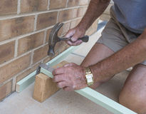 Elderly Man Hammering a Nail. Stock Images
