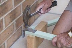 Elderly Man Hammering Nails. Royalty Free Stock Photography