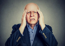 Elderly man with hands on his temples has a headache stock photos