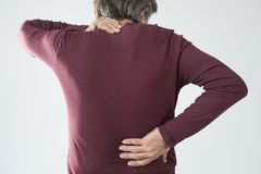 Elderly man has back and neck pain royalty free stock photo
