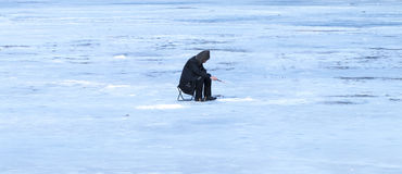 Elderly man has been fishing in the winter on the lake Stock Photo