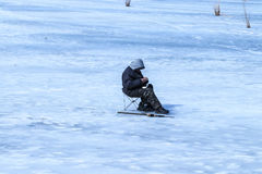Elderly man has been fishing in the winter on the lake Royalty Free Stock Photo