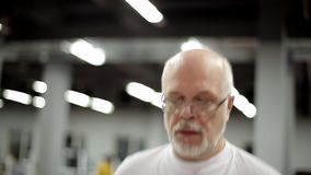 Elderly man has a treadmill. In gym stock video