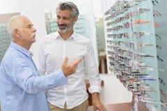 Elderly man having difficulty in choosing eyewear. Elderly men having difficulty in choosing an eyewear Royalty Free Stock Photography
