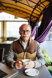 Elderly man having an espresso on a terrace of cafe. Elderly man having an espresso on a terrace Royalty Free Stock Photo