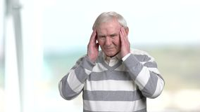 Elderly man having migraine. Old man touching his head with hands, suffering from headache stock footage