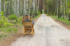 Elderly man is having rest in fores. T sitting on a wicker rocking-chair Royalty Free Stock Images
