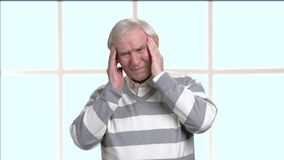 Elderly man having terrible migraine. Sad senior person suffering from strong headache, blurred background. Seniors and health problems stock video footage