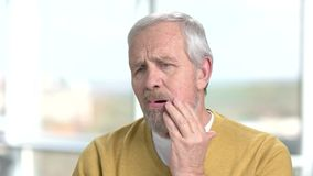 Elderly man having terrible toothache. Close up senior man with sudden tooth pain on blurred background. Dental care and stomatology stock video footage