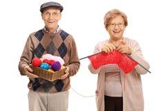 Elderly man helping an elderly woman knit. Elderly men helping an elderly women knit isolated on white background Stock Photography