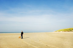 Elderly man with his dog at the beach Stock Images