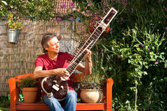 Elderly man in his garden is playing a sitar Royalty Free Stock Photography