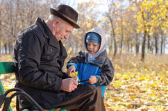 Elderly man with his grandson in the park. Elderly men with his grandson in park sitting on wooden bench smiling at something on tablet computer that youngster royalty free stock images