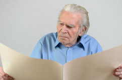 Elderly man holding a blank big ocher paper sheet Royalty Free Stock Photo