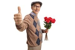 Elderly man holding a bunch of red roses showing thumbs up. Isolated on white background royalty free stock photos
