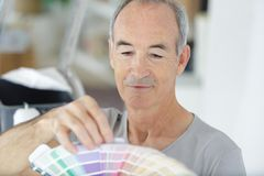 Elderly man holding color swatch. Elderly man holding a color swatch royalty free stock photography