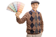 Elderly man holding a color swatch. And looking at the camera isolated on white background royalty free stock images