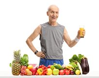 Elderly man holding a glass of juice behind a table with fruit a. Nd vegetables isolated on white background Royalty Free Stock Photos