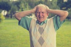 Elderly man holding his head. Stock Photo