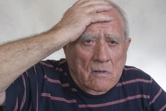 An elderly man holding his head. An older man in a striped shirt holding his head Stock Photography