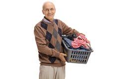 Elderly man holding a laundry basket Royalty Free Stock Photos