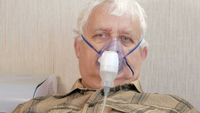 An elderly man holding a mask from an inhaler at home. Treats inflammation of the airways via nebulizer. Preventing