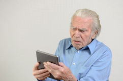 Elderly man holding a modern tablet PC Stock Images