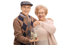 Elderly man holding money jar with elderly woman putting coin Royalty Free Stock Images