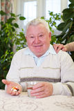 Elderly man holding pills and water Royalty Free Stock Photography