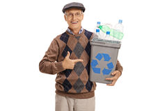 Elderly man holding a recycling bin and pointing. Cheerful elderly man holding a recycling bin full of plastic bottles and pointing isolated on white background Stock Photo