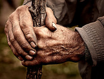 Elderly man holding a staff in his hands. Dramatic photo of an elderly man holding a staff in his hands royalty free stock images