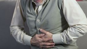 Elderly man holding stomach, feeling sharp pain, suffering from health problems. Stock footage stock video footage