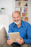 Elderly man holding a tablet-pc. Attractive smiling elderly man holding a tablet-pc as he sits on a couch in his living room at home smiling at the camera royalty free stock images