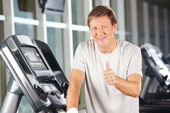 Elderly man holding thumbs up in fitness center. On a treadmill stock photography