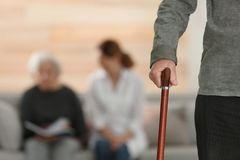 Elderly man holding walking cane and blurred caregiver with senior woman on background, focus on hand. Elderly men holding walking cane and blurred caregiver royalty free stock image