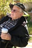 Elderly man holds coffee cup. A senior citizen, age 83, holds a cup of takeout coffee while he sits outside and enjoys the fresh air Royalty Free Stock Images
