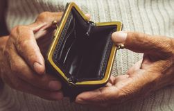 Elderly man holds in his hands an empty wallet. Vintage empty pu. Rse in wrinkled hands . Poverty in retirement concept. Special toning Stock Photos