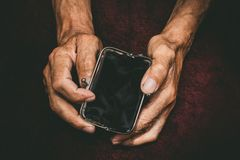 Elderly man holds in his hands an empty wallet. Vintage empty purse in wrinkled hands . Poverty in retirement concept. Special toning Royalty Free Stock Photos