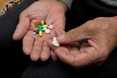 An elderly man holds a lot of colored pills in old hands. Painful old age. Health care of older people. An elderly man holds a lot of colored pills in old hands royalty free stock images