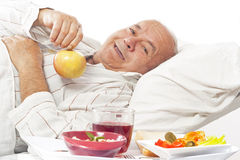 Elderly man in  hospital bed eating Royalty Free Stock Photo