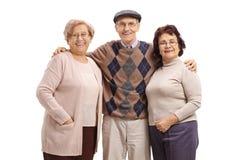 Elderly man hugging two elderly women and looking at the camera. Elderly men hugging two elderly women and looking at the camera isolated on white background stock photo
