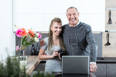 Elderly man hugging young woman. Elderly men hugging beautiful young women with DSLR camera, like father and daughter, posing at camera and laughing, standing in Stock Photos