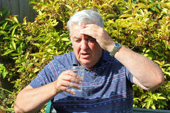 Elderly man ill drinking water. An elderly man feeling unwell and drinking a glass of water. His hand his held to his forehead Royalty Free Stock Image