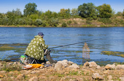 An elderly man in a jacket, baseball cap and rubber boots fishin Stock Image