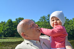 The elderly man keeps on hands the little granddaughter in park Royalty Free Stock Photo