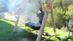 An elderly man kindles a brazier for barbecue in a beautiful courtyard stock video