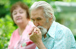 Elderly man kisses a hand of the wife. Pensioner holds a hand of the wife and kisses it against a green garden Stock Photos