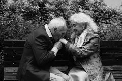 Elderly man kisses hands of the elderly woman. Black and White. Elderly couple sitting on a bench outdoors. Elderly men kisses hands of the elderly woman. Black Royalty Free Stock Images