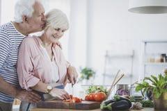 Elderly man kissing wife. Elderly men kissing wife cutting tomatoe for healthy dinner Stock Photo