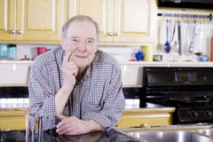 Elderly man in kitchen. Elderly man leaning on counter royalty free stock photography